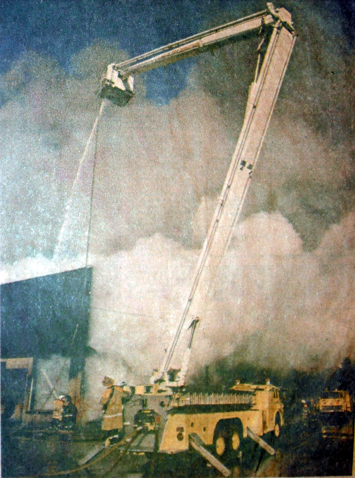 Fire fighters with snorkel truck putting out hot spots.