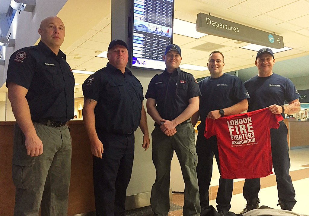 Five London Fire fighters pose as they are getting ready to fly out to Alberta