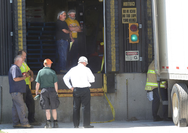 Workers looking at te accident scene around a loading dock