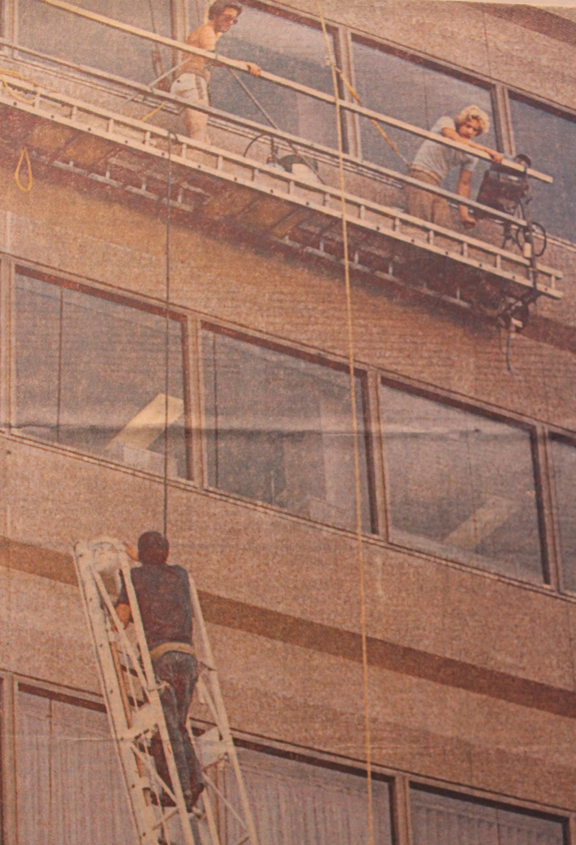Two stranded window washers talking to a firefighter on a ladder approximately 110 feet on the side of a building.